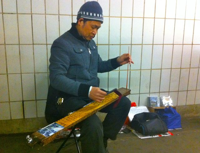 Zong Li Lu, playing a monochord in the Grand Street subway station in Chinatown. | westvirginiaville.com photo